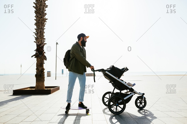 Father skate boarding with his baby in stroller.