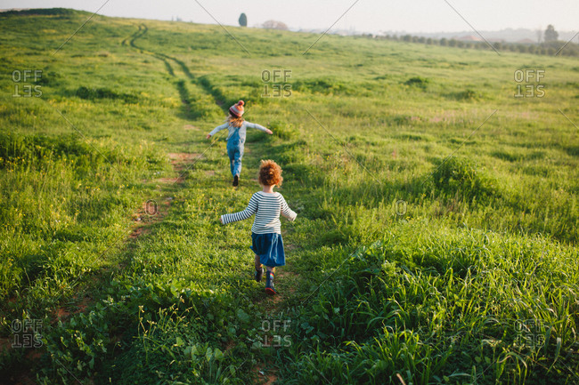 Two sisters running up a green hill