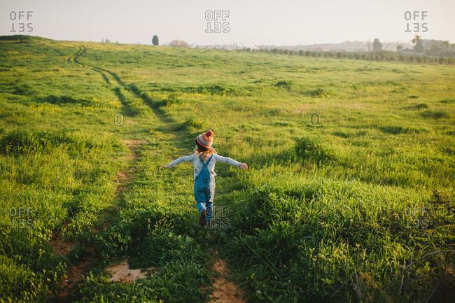 A girl running up a green hill