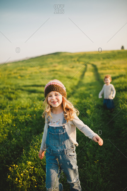 Two sisters walking down a green hill