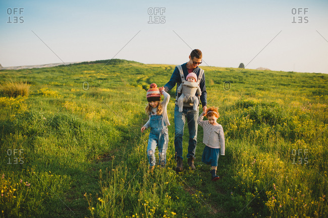 A father and his three daughters walking down a green field