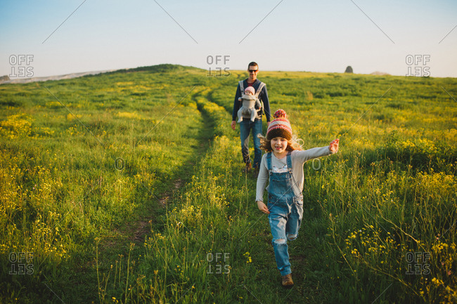 Girl leading her family running down a green hill