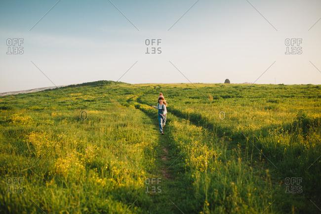 A girl running down a green hill