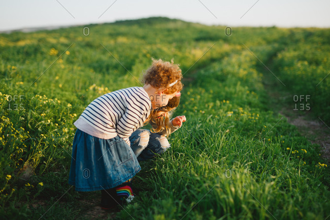 Two sisters exploring nature in a green field
