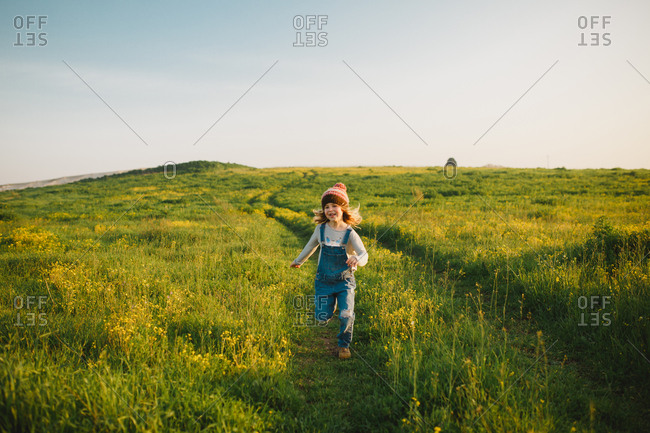 A girl running down a green hill