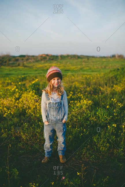Girl wearing blue jeans overall standing in a green field