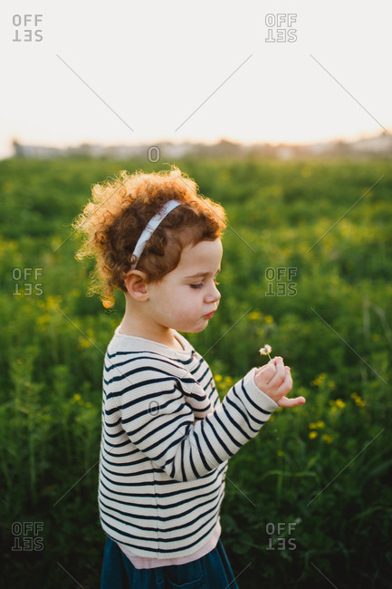 Girl blowing dandelion while standing on a green field