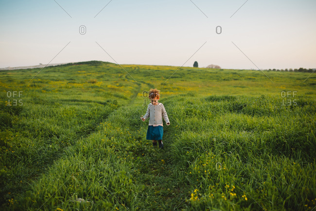 A girl walking down a green hill