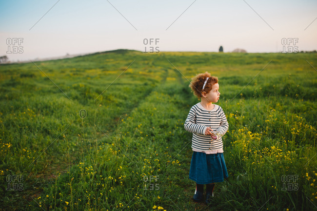 A girl standing on a green field