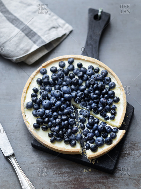 Blueberry tart with one piece sliced