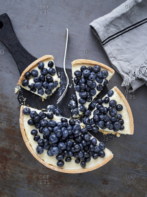 Overhead view of a blueberry tart partially eaten