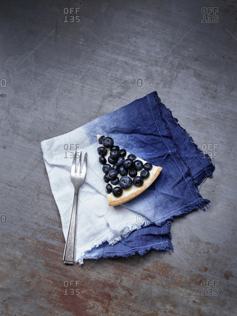 Slice of a blueberry tart on a linen napkin
