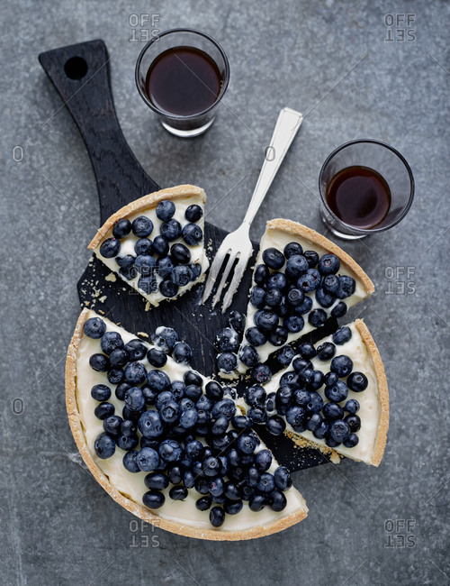 Overhead view of a blueberry tart partially eaten with drinks