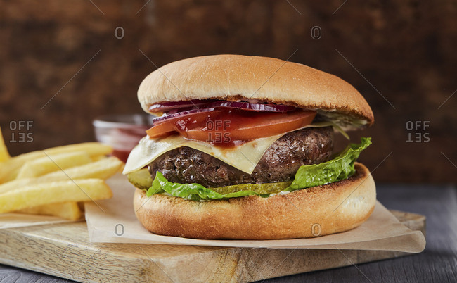 Succulent cheeseburger served on chopping board