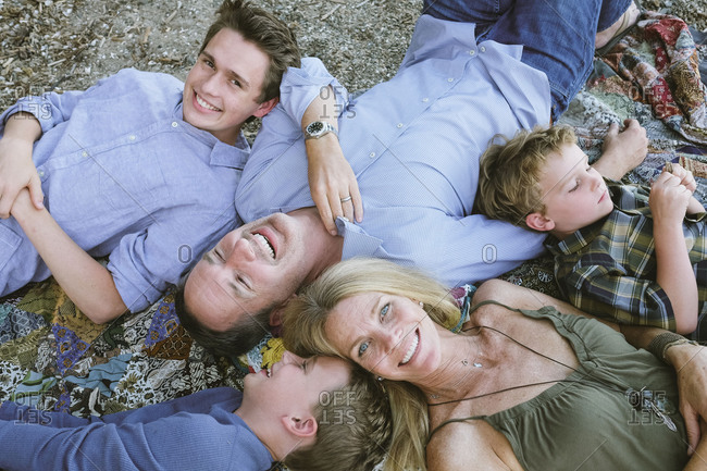 Overhead portrait of five person family lying on their backs outside