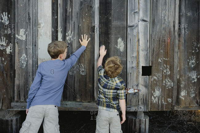 Back view of two brothers pressing painted handprints into outdoor shed wall