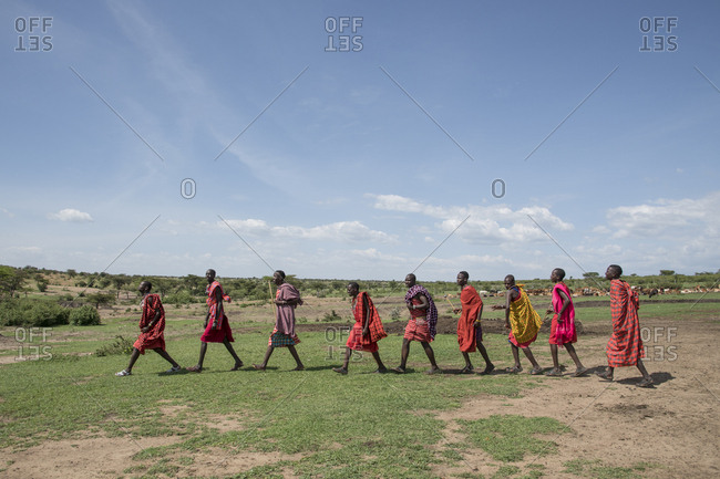Maasai Mara, Kenya - January 23, 2018: Maasai villagers walking across savannah