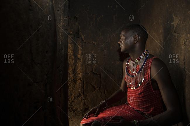 Maasai villager sitting in the entrance to a mud hut, Maasai Mara, Kenya
