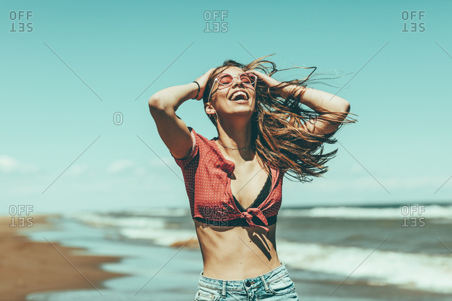 Carefree woman having a great time alone on the beach