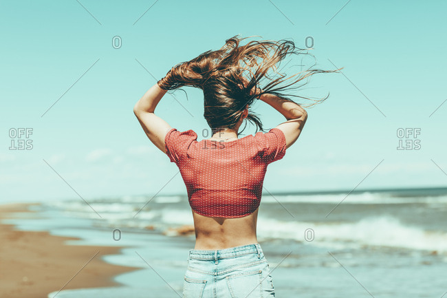 Back view of fit woman in crop-top holding hair out of wind on the beach