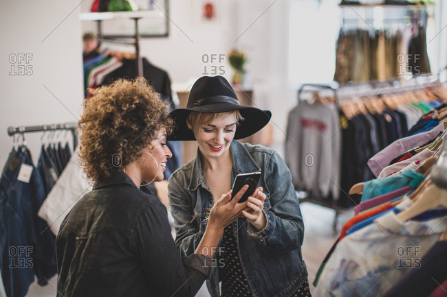 Millennial female friends looking at a smartphone in a vintage clothing store