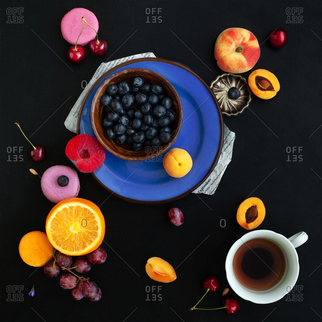 Composition with food and berries on black background inspired by abstract painting