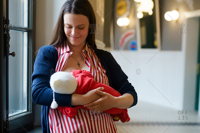 Indoor portrait of young mother in striped red dress breastfeeding toddler