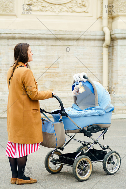 Portrait of young mother walking with baby in a blue stroller