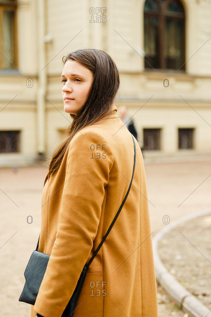 Portrait of young brunette girl walking on the street dressed in beige coat