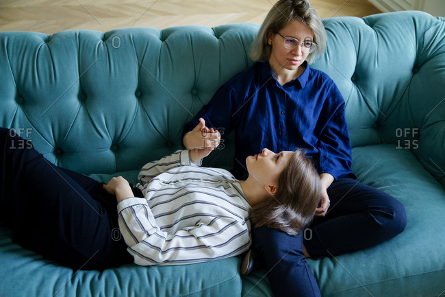 Lesbian couple spend their time lying on the couch together at home