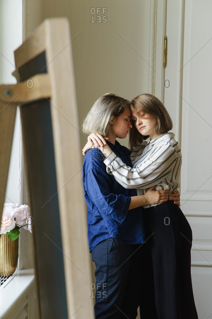 Lesbian couple embracing one another at beautiful home