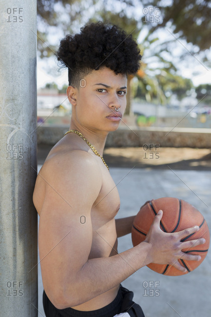 Portrait of young Latin male holding a basketball ball looking at camera