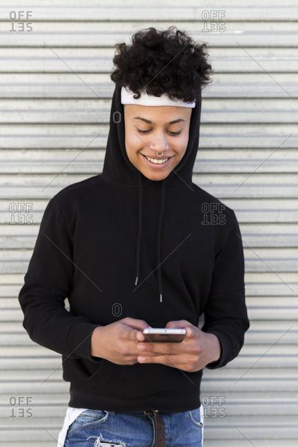 Portrait stylish Latin male using smart phone