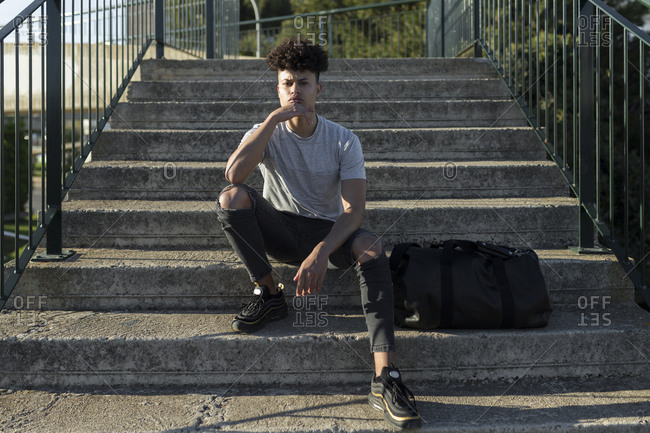 Portrait of confident stylish Latin young male sitting on stairs in the city