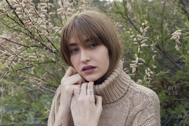 Portrait of fashionable young woman wearing long neck jumper against autumn flowers in nature