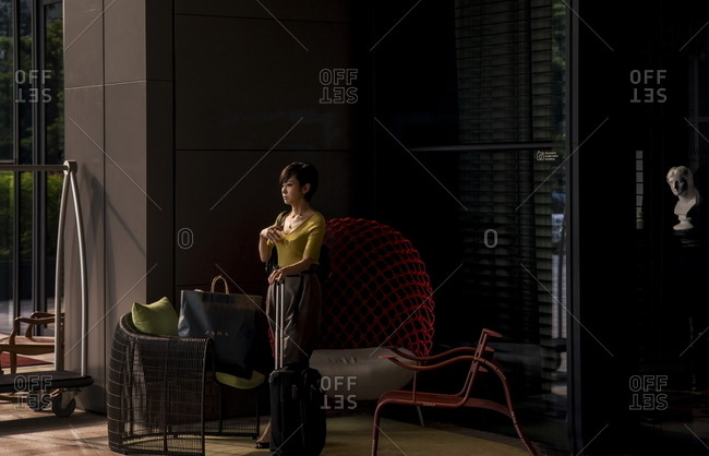 Singapore - October 20, 2017: Woman with suitcase standing in lobby of Marriott Hotel