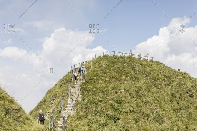 Ticino, Switzerland - July 14, 2017: People climbing the staircase to the grassy summit of Monte Generoso