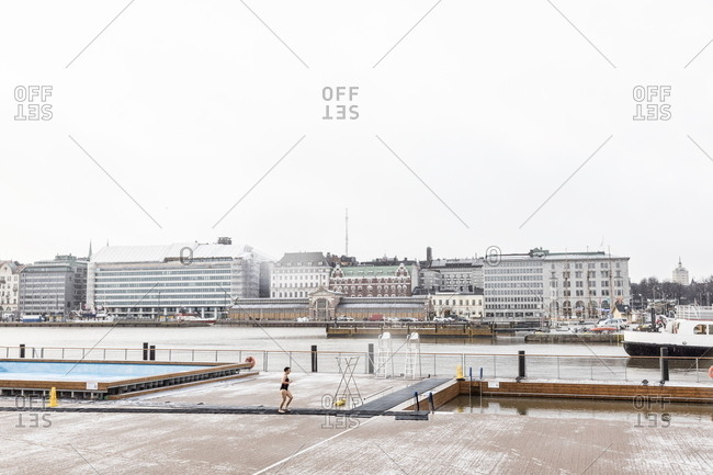 Helsinki, Finland - November 26, 2017: Woman walking between swimming pools at Allas Sea Pool