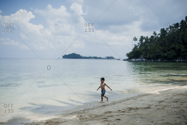 Boy playing in the tide on beach in Malaysia