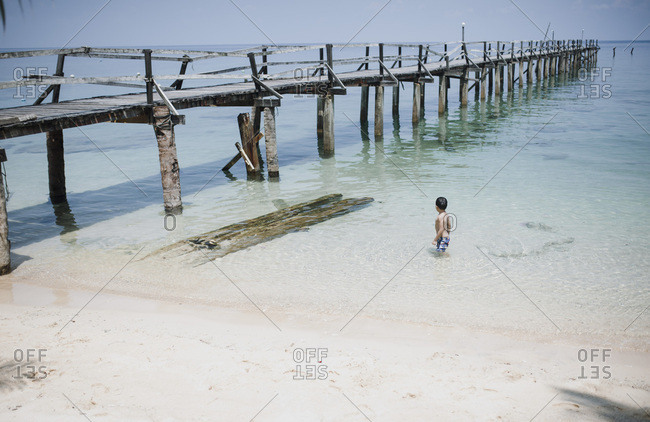 Boy swimming near pier at a beach in Malaysia
