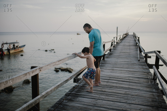 Father and son walking on a boardwalk