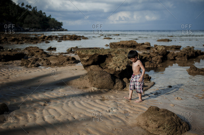 Boy playing on the coast of a beach in Malaysia