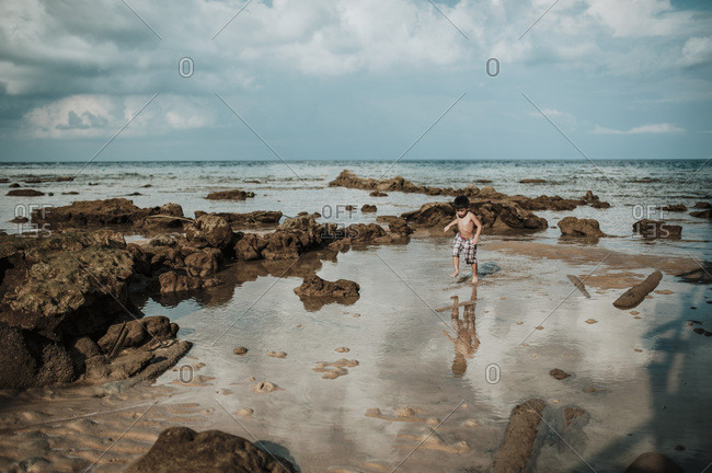 Boy playing in tide on beach in Malaysia