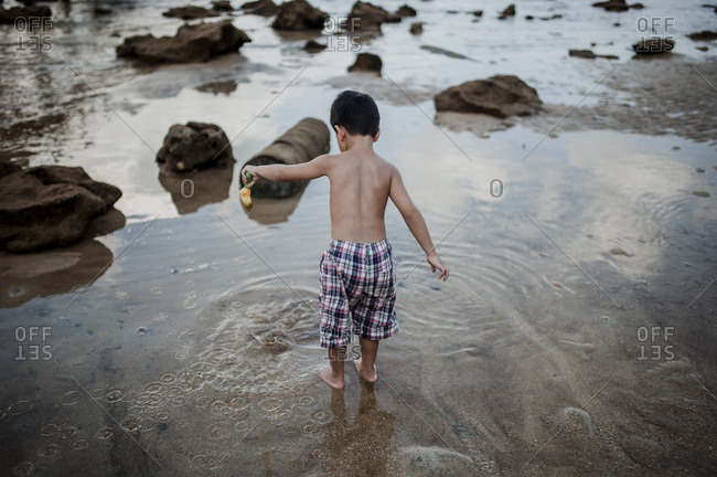 Boy playing in the water at beach in Malaysia