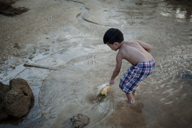 Boy playing in the water on the coast of Malaysia