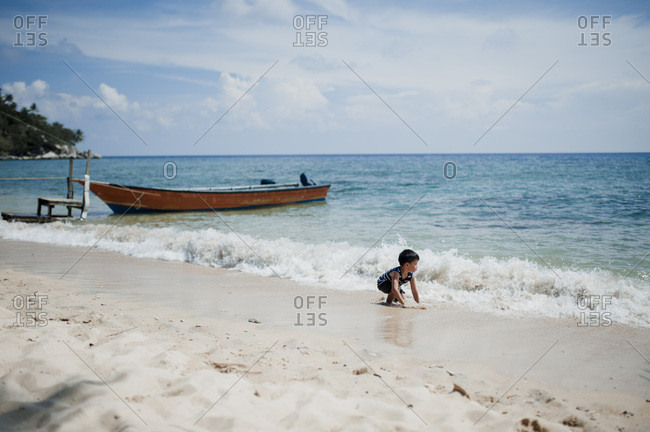 Boy playing in the waves on a beach in Malaysia