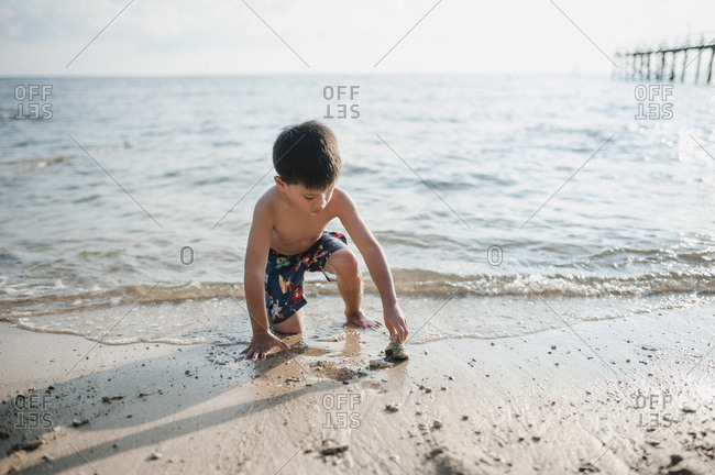 Boy looking at a seashell on a beach in Malaysia