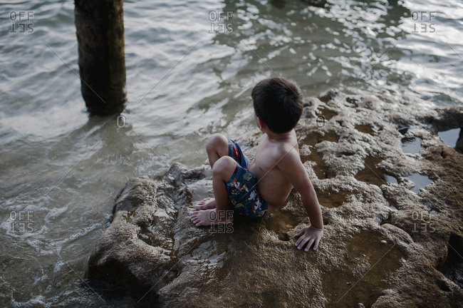 Boy playing on rocks in tide on beach in Malaysia