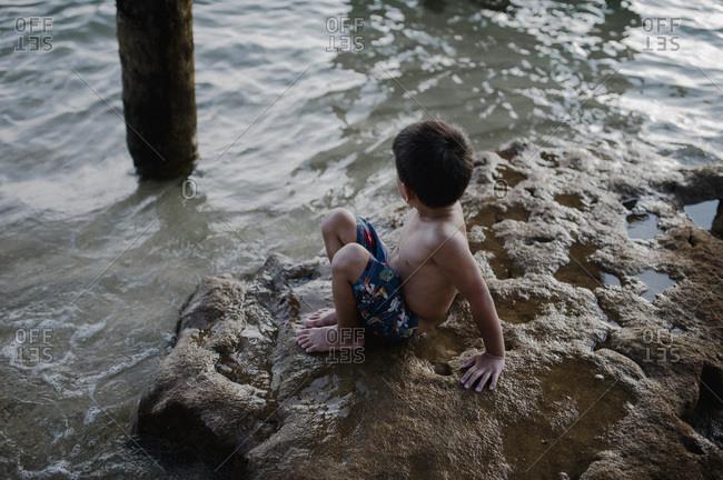 Boy playing on rocks in tide on beach in Malaysia