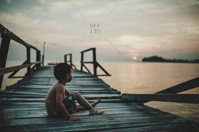 Little boy on a pier at a beach in Malaysia watching the sunset